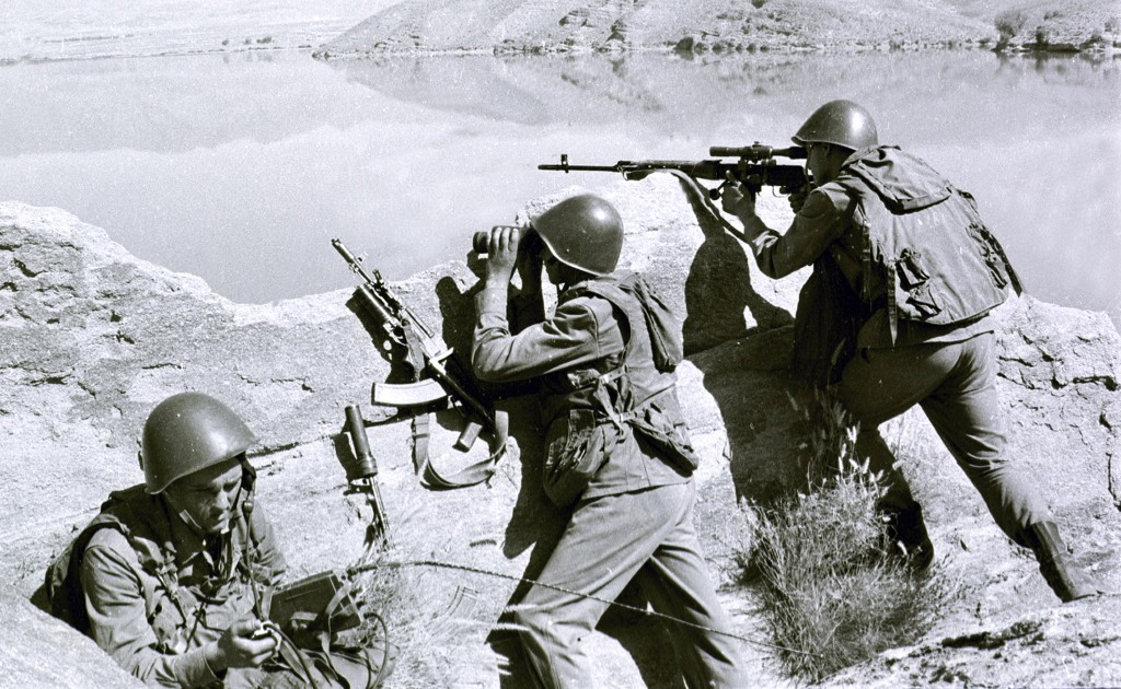 FILE - In this late April 1988, file photo, Soviet soldiers observe the highlands, while fighting Islamic guerrillas at an undisclosed location in Afg
