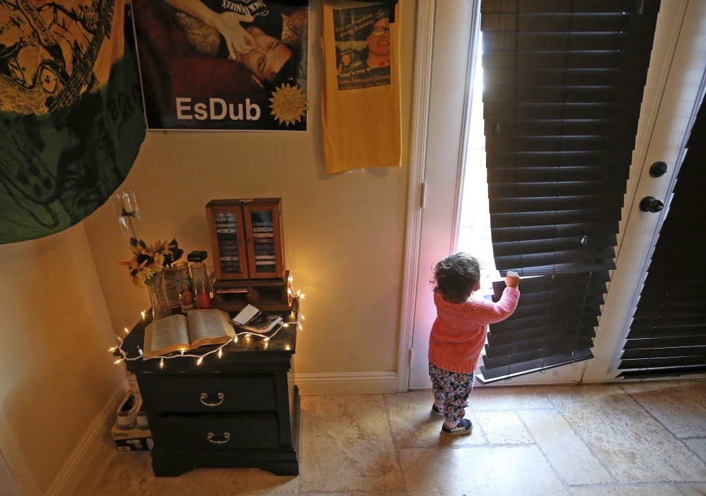 Athena Chavez, 2, the daughter of Aaron Francisco Chavez, looks out a nearby door as she stands next to a shrine for Aaron at the family home Wednesda...