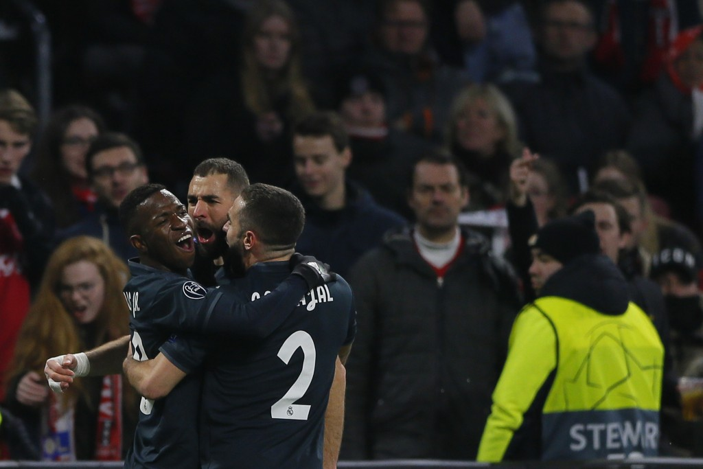 Real forward Karim Benzema, center, celebrates with his teammates after scoring his side's opening goal during the first leg, round of sixteen, Champi...