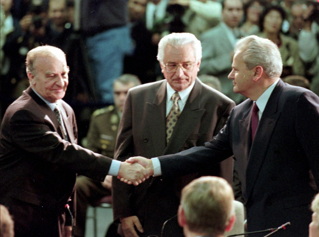 FILE - In this Nov. 1, 1995 file photo, President of Bosnia Alija Izetbegovic, left, shakes hands with Serbian President Slobodan Milosevic, right, as...