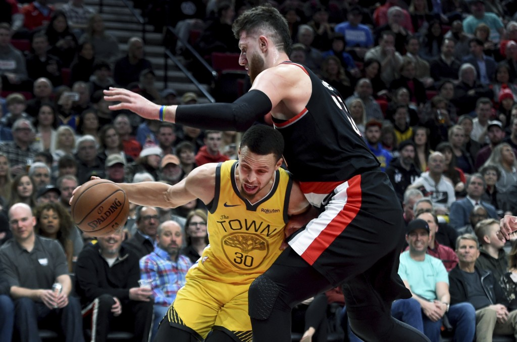 Golden State Warriors guard Stephen Curry, left, tries to get around Portland Trail Blazers center Jusuf Nurkic during the first half of an NBA basket...