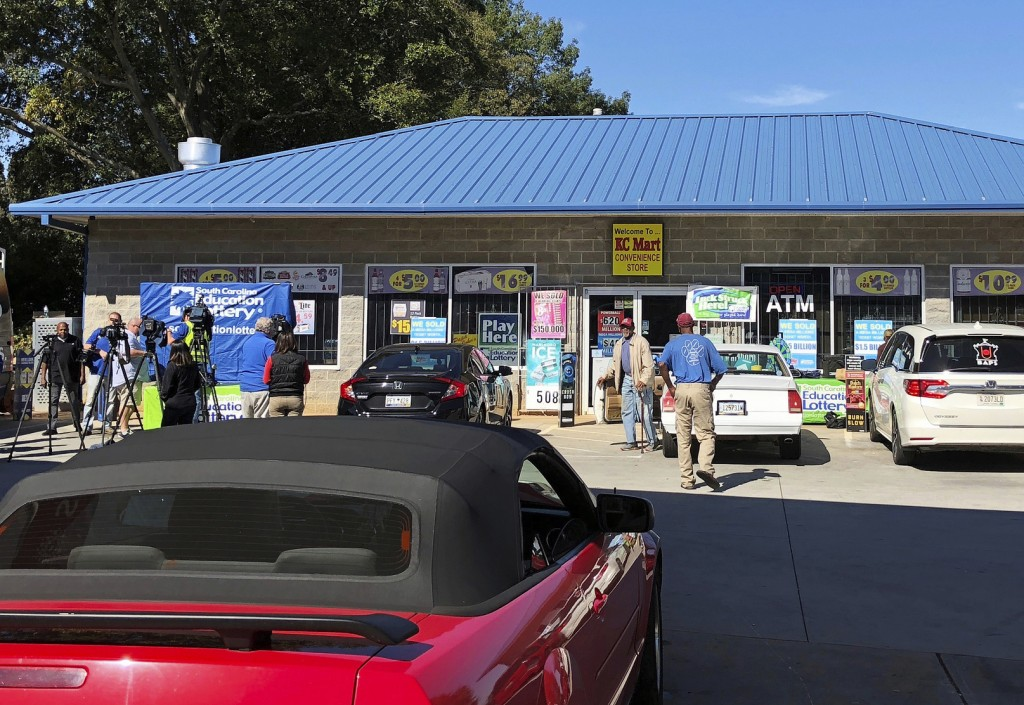 FILE - In this Oct. 24, 2018, file photo, media, left record people entering the KC Mart in Simpsonville, S.C., after it was announced the winning Meg...