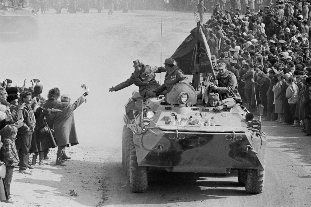In this photo taken on Feb. 15, 1989, people and relatives greet Soviet Army soldiers driving on their armored personnel carriers after crossing a bri...