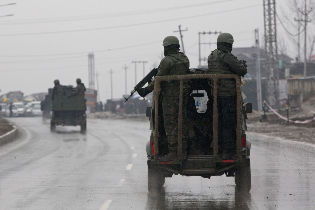 Indian army soldiers leave after inspecting the the site of an explosion in Pampore, Indian-controlled Kashmir, Thursday, Feb. 14, 2019. Security offi...