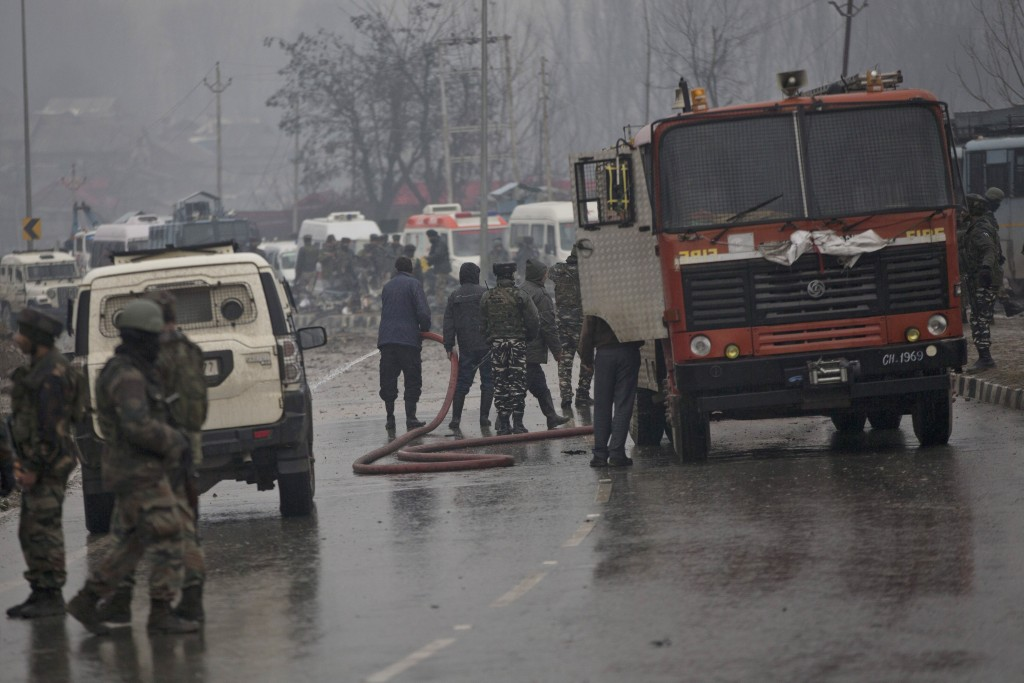 Indian firemen spray water on a road to wash away blood after an explosion in Pampore, Indian-controlled Kashmir, Thursday, Feb. 14, 2019. Security of...