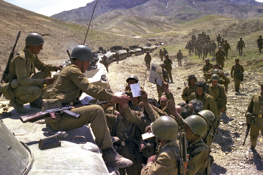 In this undated photo, Soviet soldiers get fresh newspapers and mail while a convoy stoped somewhere in Afghanistan. When the Soviet Union completed i...