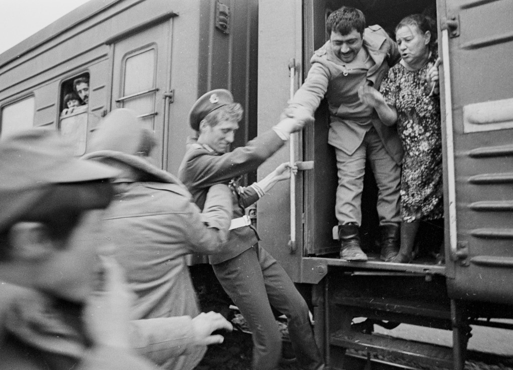 In this photo taken on Feb. 15, 1989, Soviet Army soldiers help each other to catch a train home after crossing a bridge on the border between Afghani...