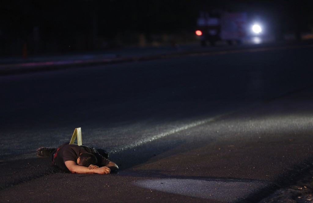 FILE - In this June 29, 2017 file photo, the body of a man who was shot dead lies on a road in Navolato, on the outskirts of Culiacan, Sinaloa state,