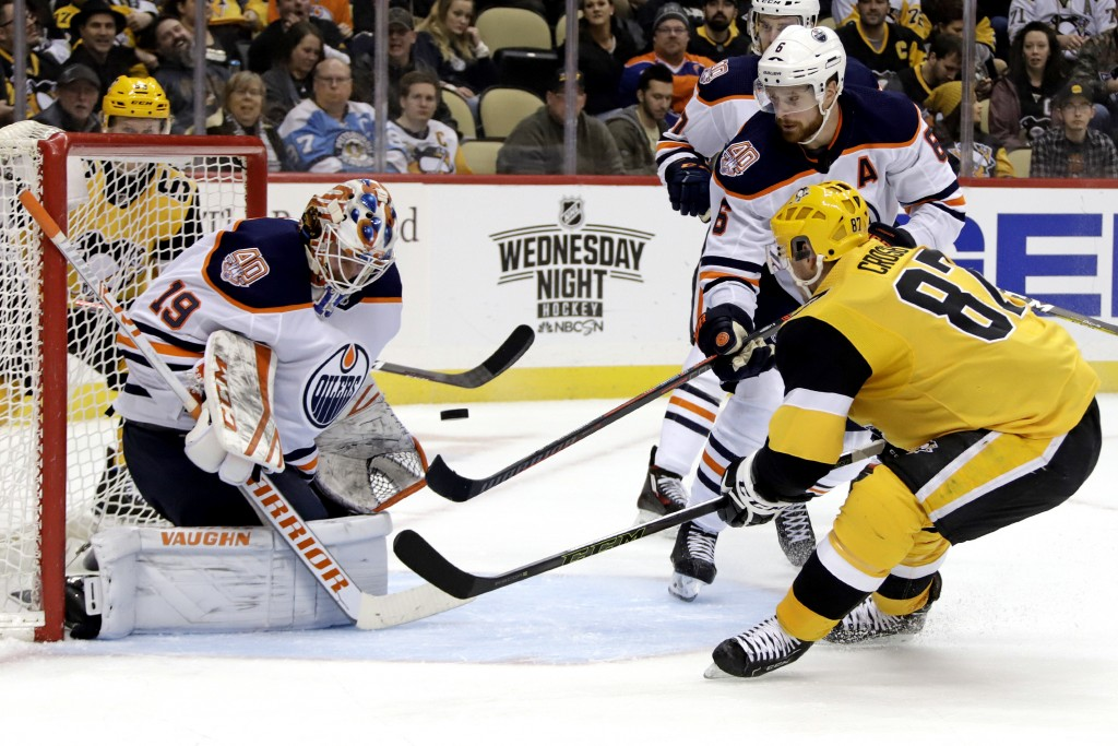 Pittsburgh Penguins' Sidney Crosby (87) can't get his stick on a rebound in front of Edmonton Oilers goaltender Mikko Koskinen (19) with Adam Larsson