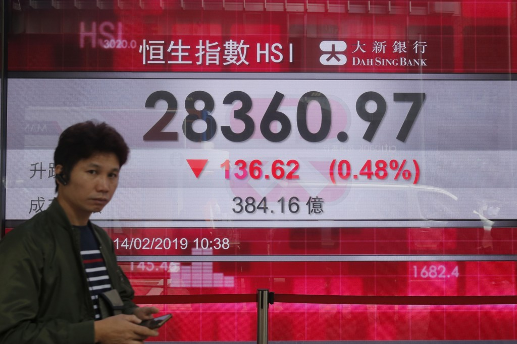 A man walks past an electronic board showing Hong Kong share index outside a bank in Hong Kong, Thursday, Feb. 14, 2019. Asian stocks were mostly lowe