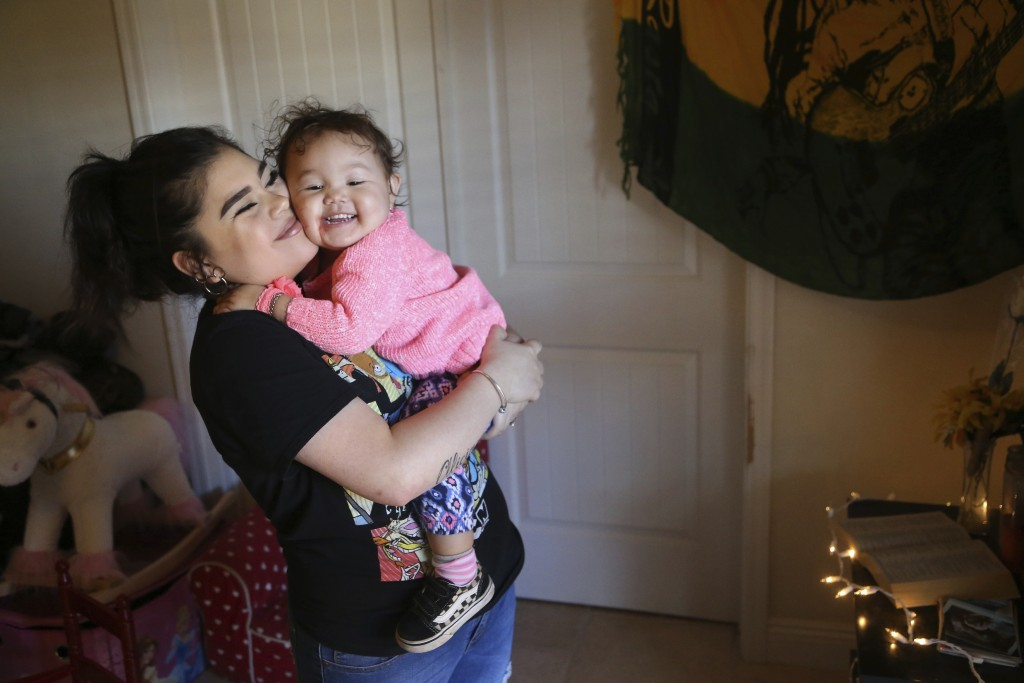 Seanna Leilani Chavez, left, holds Athena Chavez, 2, the sister and daughter of Aaron Francisco Chavez respectively, as the two stand next to a shrine...