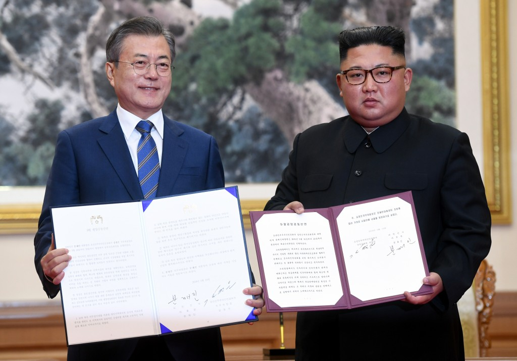 FILE - In this Sept. 19, 2018 photo, South Korean President Moon Jae-in, left, and North Korean leader Kim Jong Un hold the documents after signing at...