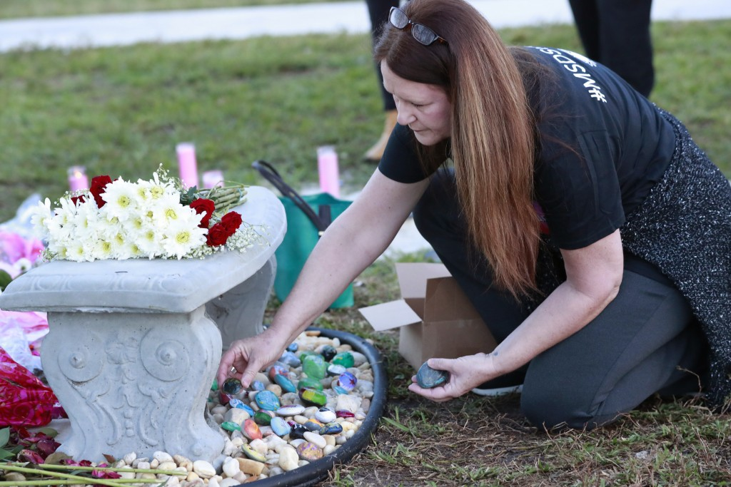 Suzanne Devine Clark, an art teacher at Deerfield Beach Elementary School, places painted stones at a memorial outside Marjory Stoneman Douglas High S...
