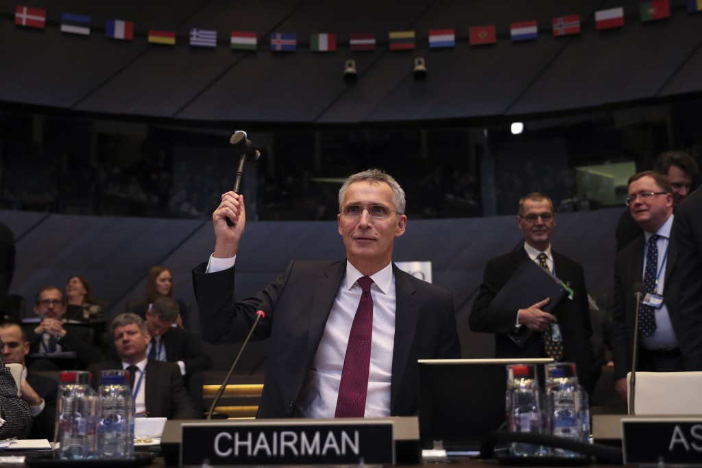 NATO Secretary General Jens Stoltenberg bangs a gavel to signal the start of a meeting of NATO defence ministers at NATO headquarters in Brussels, Wed