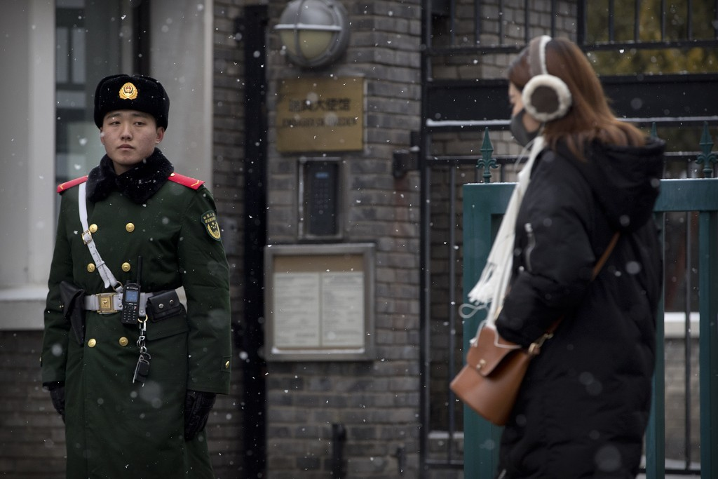 A paramilitary police officer watches as a pedestrian walks past the gate of the Swedish Embassy in Beijing, Thursday, Feb. 14, 2019. The embassy said