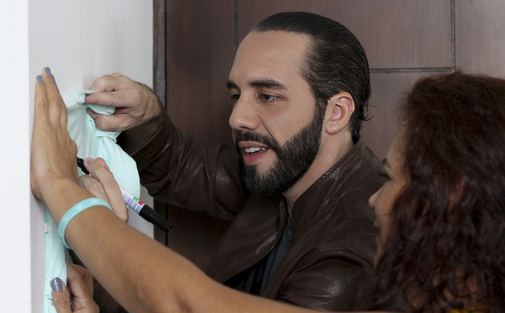 Salvadoran President-elect Nayib Bukele, autographs a T-shirt after an interview with The Associated Press in San Salvador, El Salvador, Tuesday, Feb.