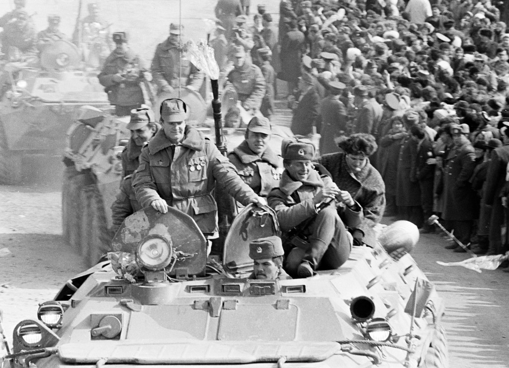 In this photo taken on Wednesday, Feb. 15, 1989, Soviet Army soldiers ride armored personnel carriers after their unit crossed a bridge on the border