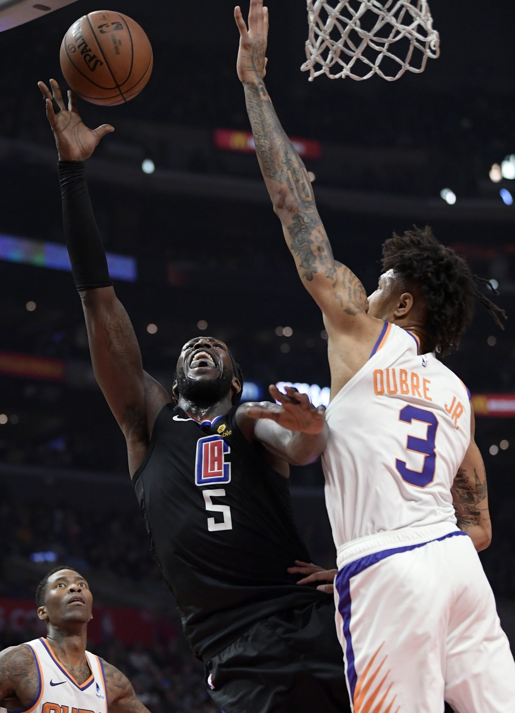 Los Angeles Clippers forward Montrezl Harrell, center, shoots as Phoenix Suns forward Kelly Oubre Jr., right, defends and guard Jamal Crawford watches