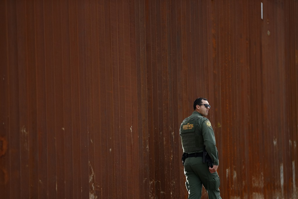 FILE - In this Jan 15, 2019, file photo, a U.S. Border Patrol agent walks in front of a section of newly-replaced border wall in San Diego. President ...