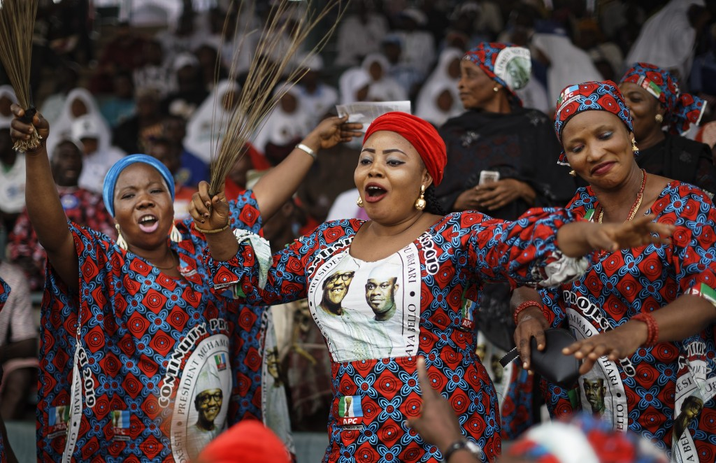 Supporters of incumbent President Muhammadu Buhari sing and dance in advance of his arrival at a campaign rally in Abuja, Nigeria Wednesday, Feb. 13,