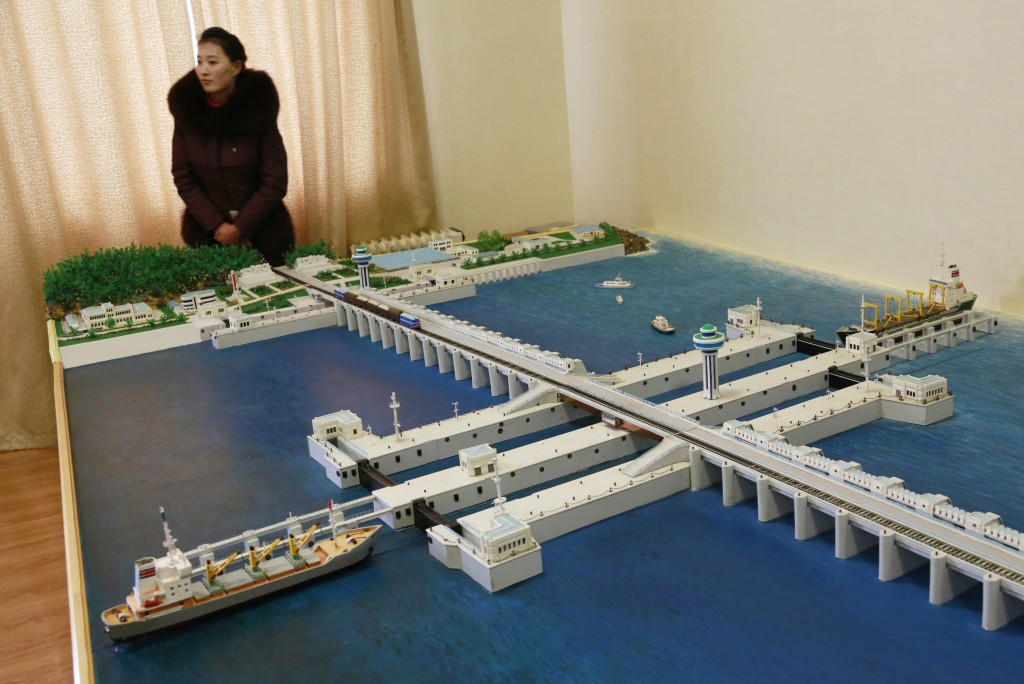 In this Feb. 2, 2019 photo, a guide stands next to a model of the West Sea Barrage in Nampo, North Korea. North Korea is exploring two ambitious alter