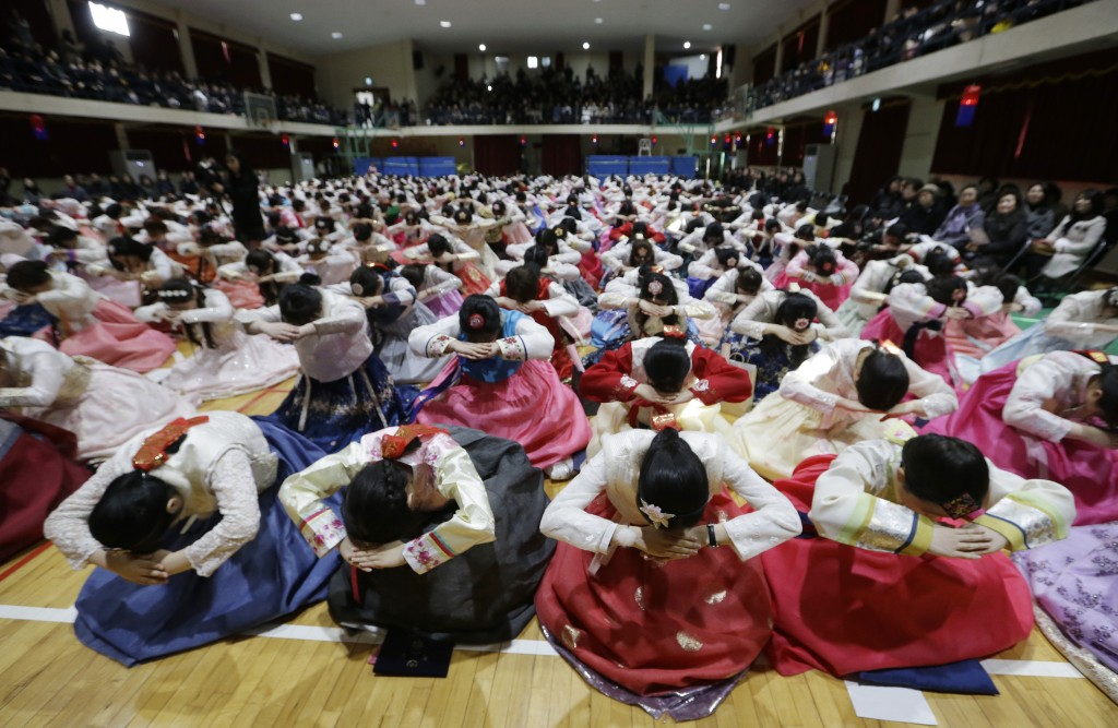 In this Thursday, Feb. 14, 2019, file photo, South Korean seniors clad in traditional attire bow during a joint graduation and coming-of-age ceremony ...