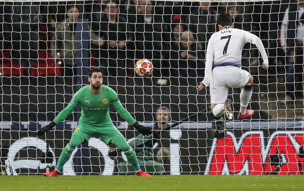 Tottenham midfielder Heung-Min Son, right, scores the opening goal against Dortmund goalkeeper Roman Buerki during the Champions League round of 16, f...