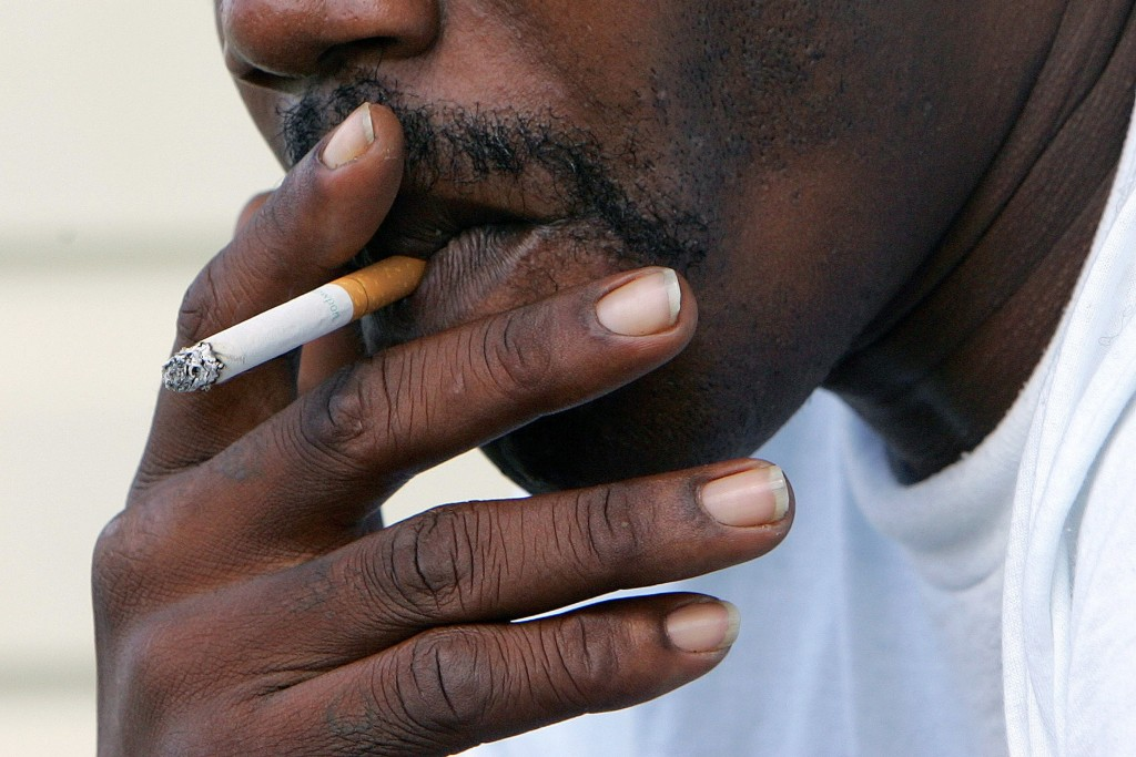 FILE - In this Oct. 4, 2005 file photo, a man smokes a cigarette in Euharlee, Ga. According to a report by the American Cancer Society released on Thu...