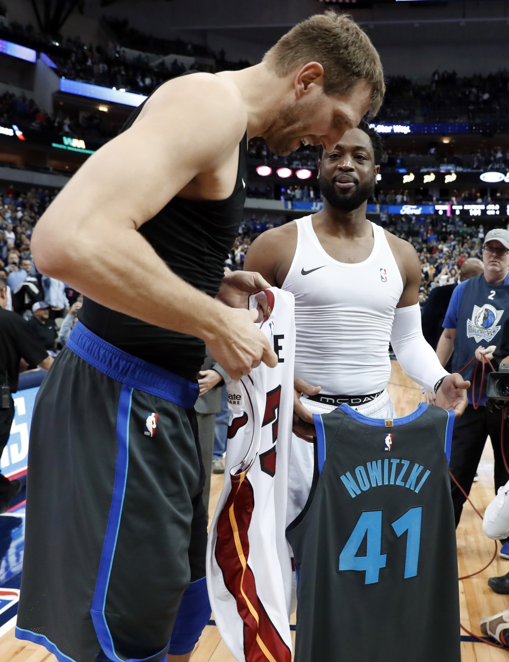 Dallas Mavericks' Dirk Nowitzki left, and Miami Heat's Dwyane Wade, second from right, talk as they swap jerseys after an NBA basketball game in Dalla...