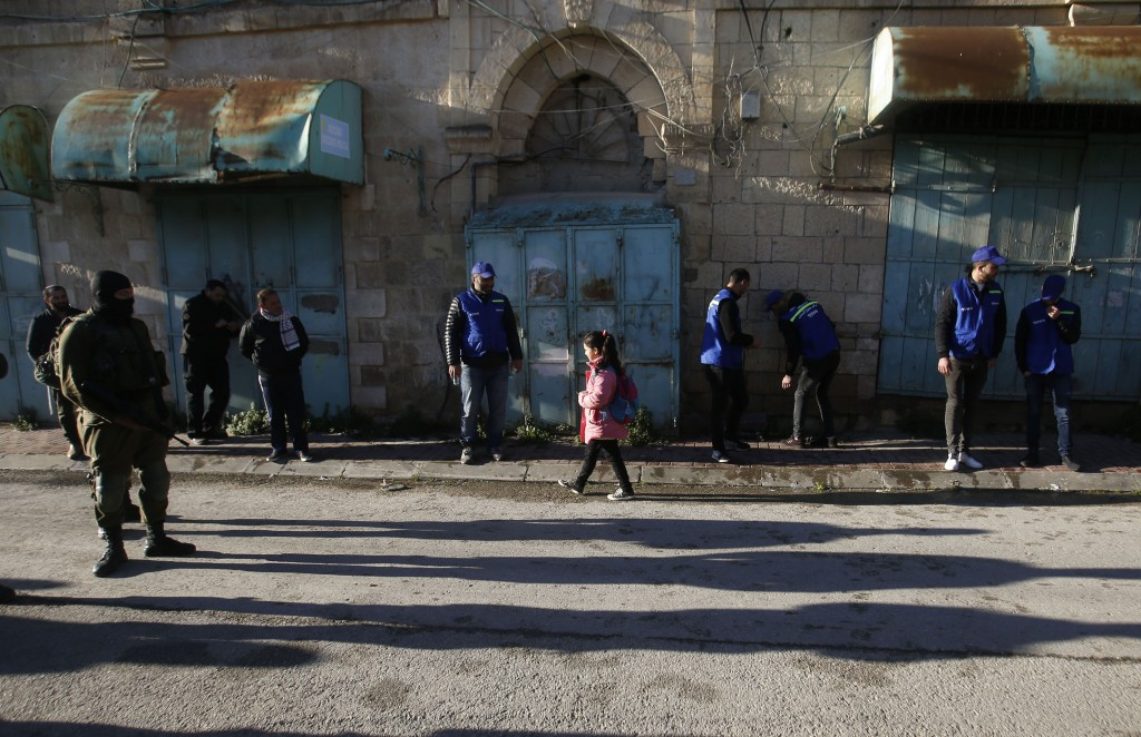 In this Tuesday, Feb. 12, 2019 photo, Palestinian observers, center, watch as children walk past Israeli soldiers on their way to school in the West B...