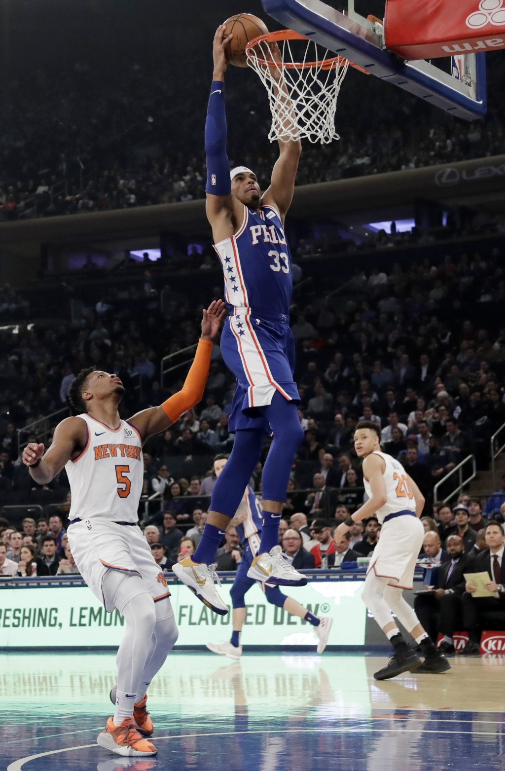 Philadelphia 76ers' Tobias Harris (33) drives past New York Knicks' Dennis Smith Jr. (5) during the first half of an NBA basketball game, Wednesday, F...