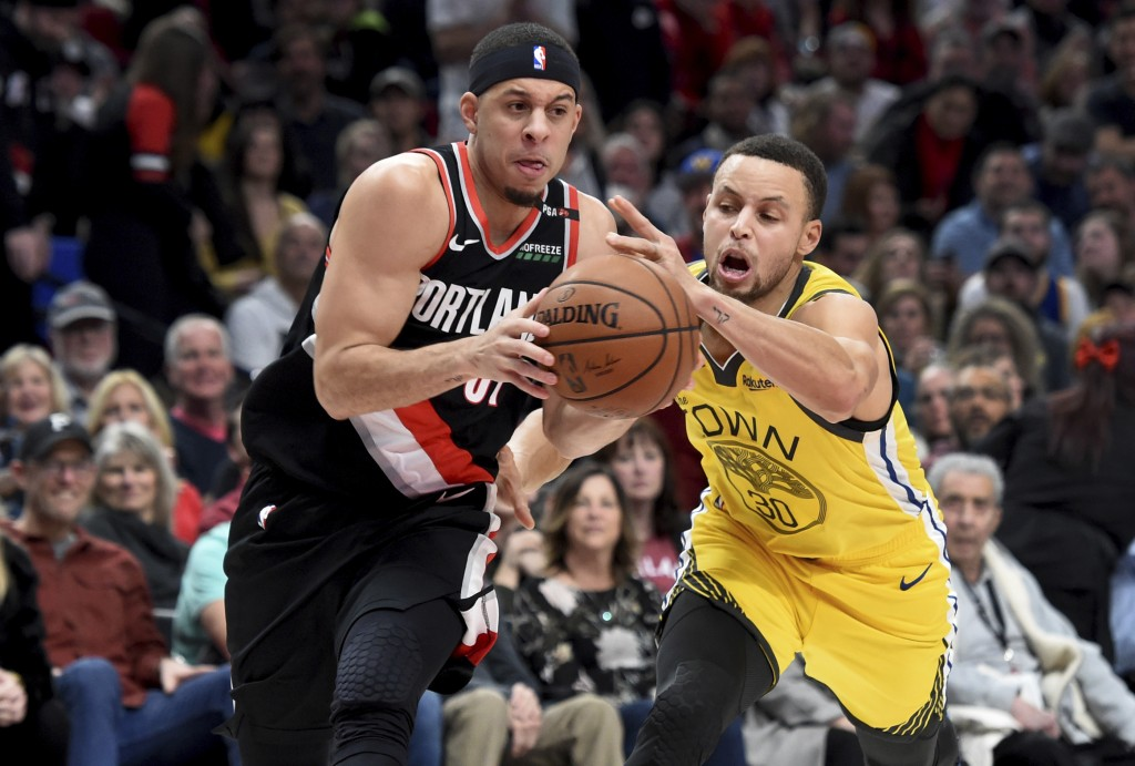 Portland Trail Blazers guard Seth Curry, left, drives to the basket on Golden State Warriors guard Stephen Curry during the second half of an NBA bask