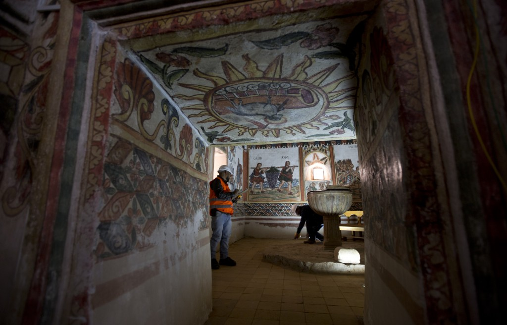 In this Feb. 9, 2019 photo, architects, experts in restoration inspect the murals of the church in Curahuara de Carangas, Bolivia. The church's larges