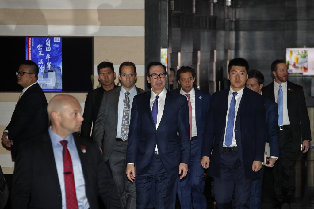 U.S. Treasury Secretary Steven Mnuchin, center, is escorted by delegations and security officers as he leaves a hotel to attend a new round of high-le