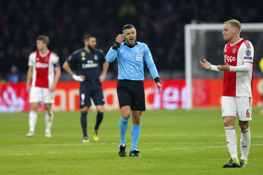 Ajax's Donny van de Beek, right, argues with referee Damir Skomina from Slovenia during the first leg, round of sixteen, Champions League soccer match...