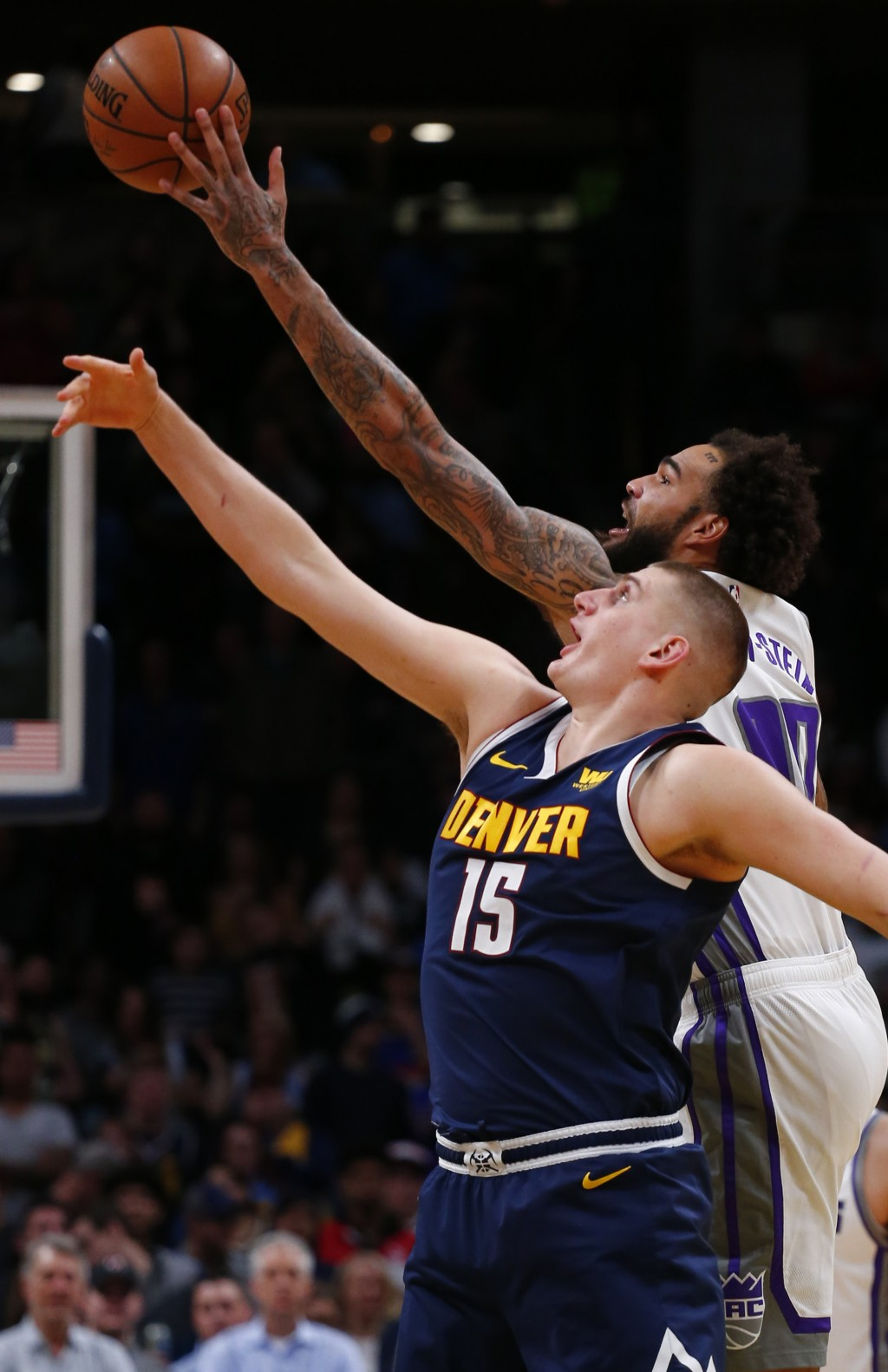 Denver Nuggets center Nikola Jokic (15) and Sacramento Kings center Willie Cauley-Stein (00) reach for the ball during the first half of an NBA basket