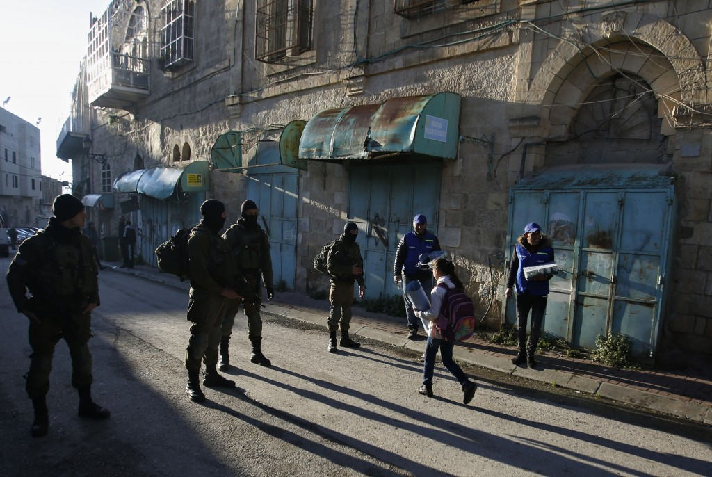 In this Tuesday, Feb. 12, 2019 photo, Palestinian observers, right, watch as children walk past Israeli soldiers on their way to school in the West Ba...