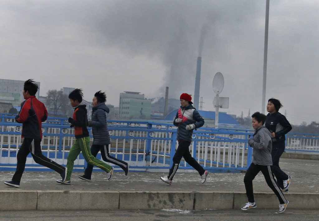 In this Dec. 15, 2018, photo, young joggers pass by as smokes billows from the stack of the Pyongyang Power Plant in Pyongyang, North Korea. North Kor