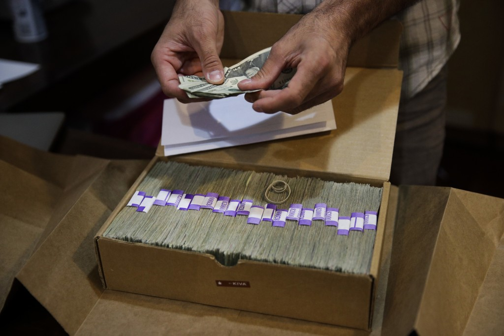 FILE - In this June 27, 2017 file photo, the proprietor of a medical marijuana dispensary prepares his monthly tax payment, over $40,000 in cash, at h