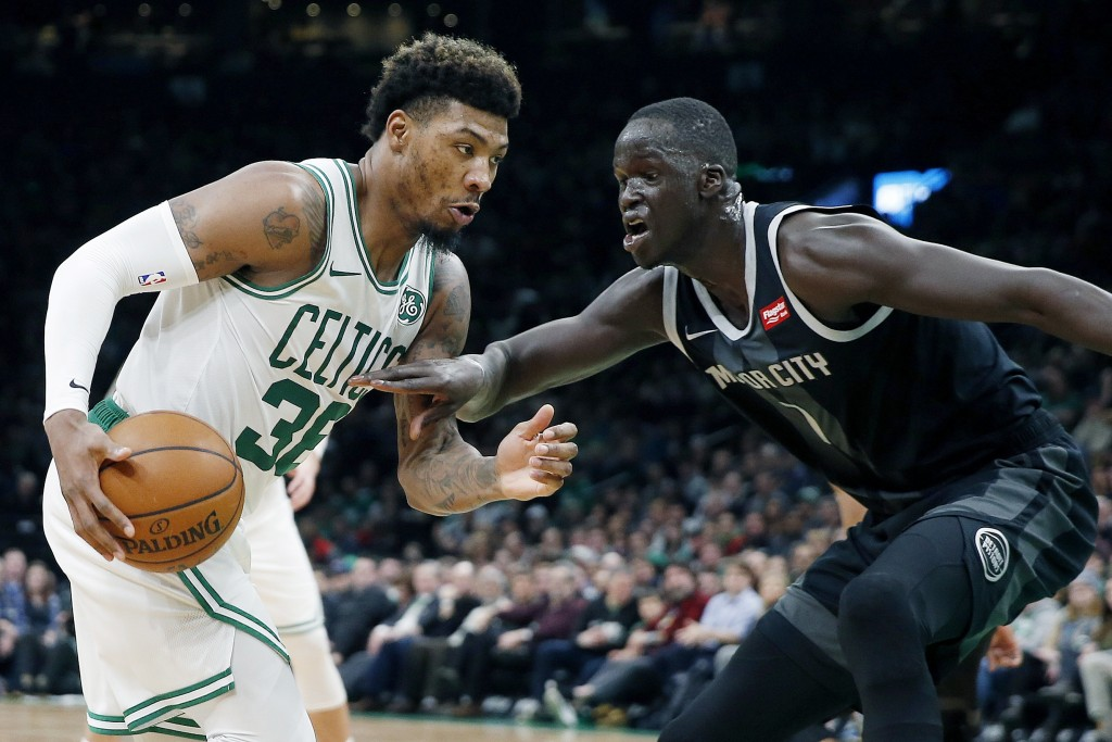 Boston Celtics' Marcus Smart, left, drives for the basket against Detroit Pistons' Thon Maker, right, during the first half of an NBA basketball game ...