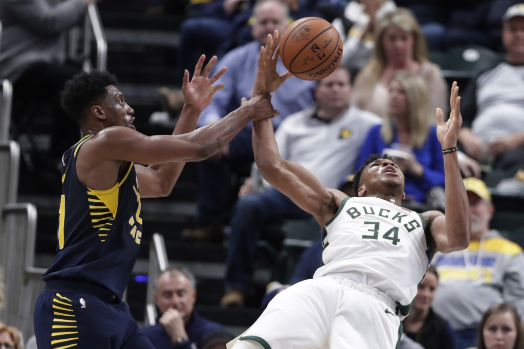 Indiana Pacers forward Thaddeus Young (21) fouls Milwaukee Bucks guard Pat Connaughton (24) during the first half of an NBA basketball game in Indiana