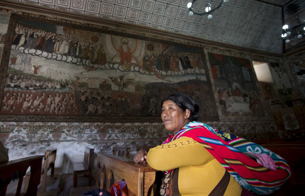 In this Feb. 9, 2019 photo, a woman attends Mass at the local church in Curahuara de Carangas, Bolivia. Curahuara de Carangas was an important center