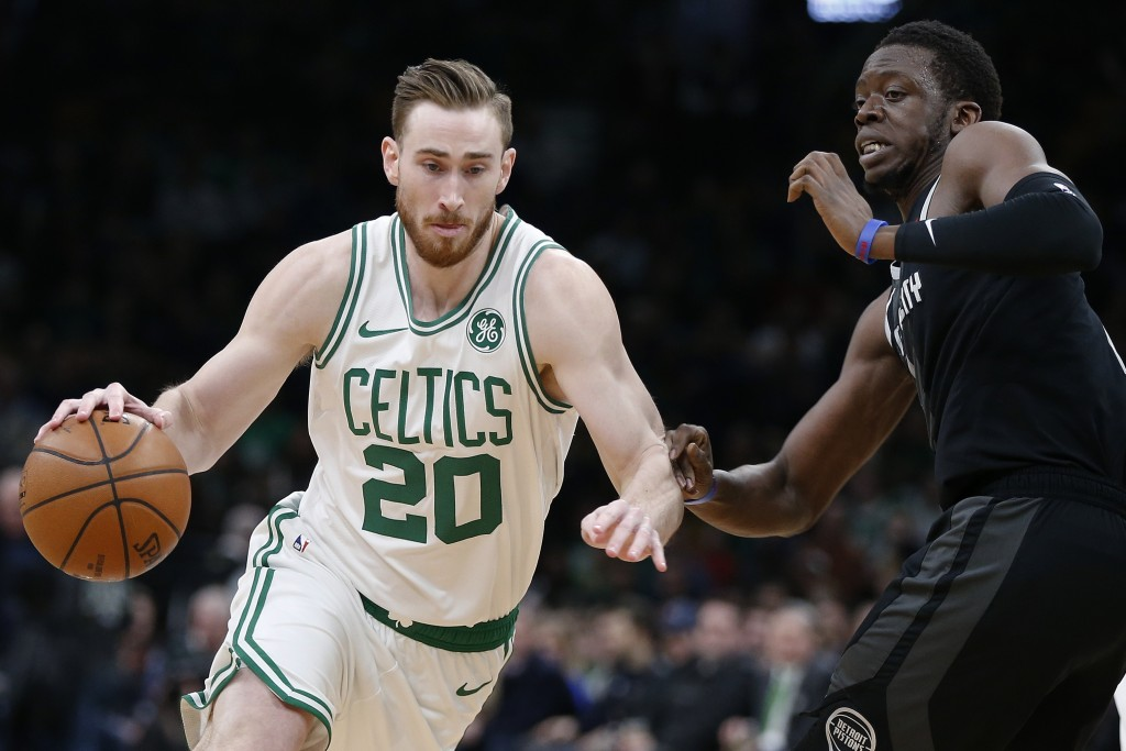 Boston Celtics' Gordon Hayward, left, drives past Detroit Pistons' Reggie Jackson, right, during the first half of an NBA basketball game in Boston, W...