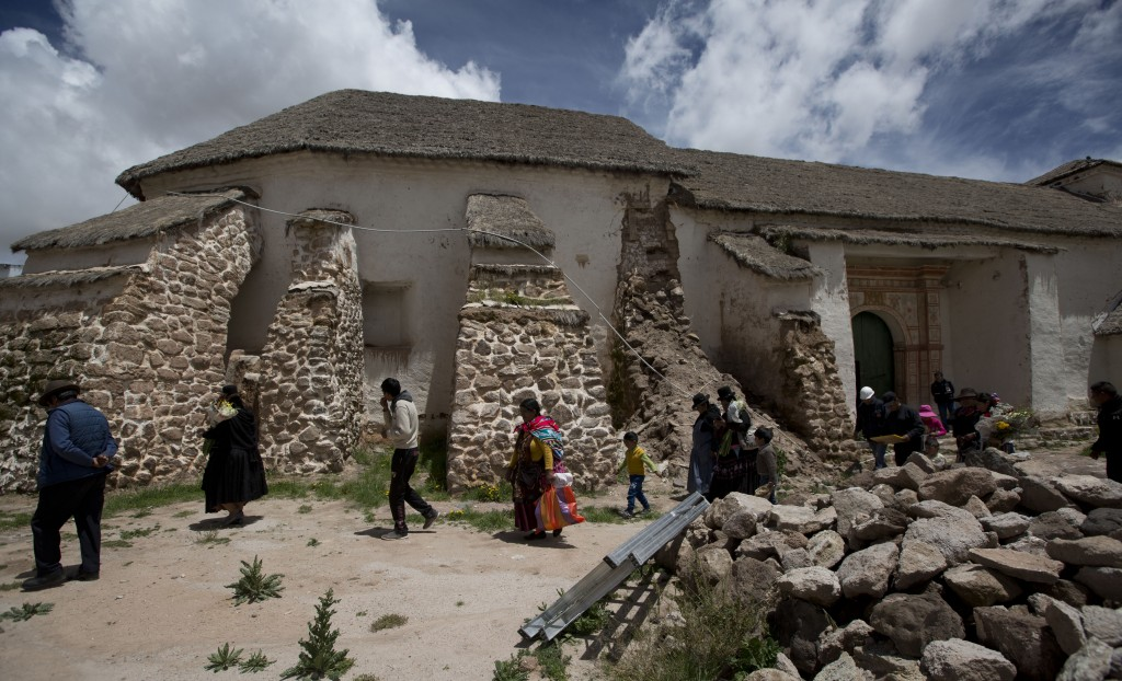 In this Feb. 9, 2019 photo, locals walk outside the church in Curahuara de Carangas, Bolivia. Heavy rains recently caused one of its buttresses to wea...