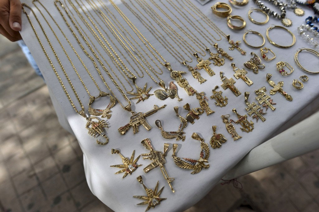 FILE - In this July 22, 2015 file photo, a man sells jewelry, many of it with narco-culture imagery, in downtown Culiacan, Mexico. U.S. officials hail