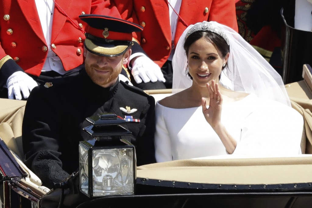 FILE - In this Saturday, May 19, 2018 file photo, Britain's Prince Harry and Meghan Markle leave Windsor Castle in a carriage after their wedding at S...