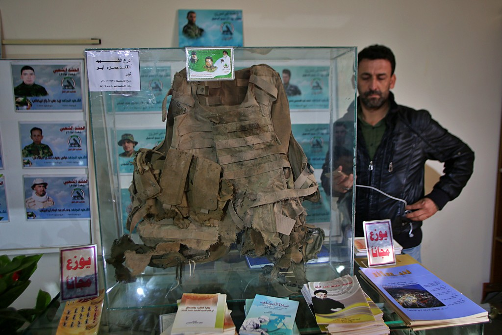 In this Friday, Feb. 1, 2019 photo, body armor shredded by shrapnel that was worn by a militiamen who died fighting the Islamic State group, is on dis...