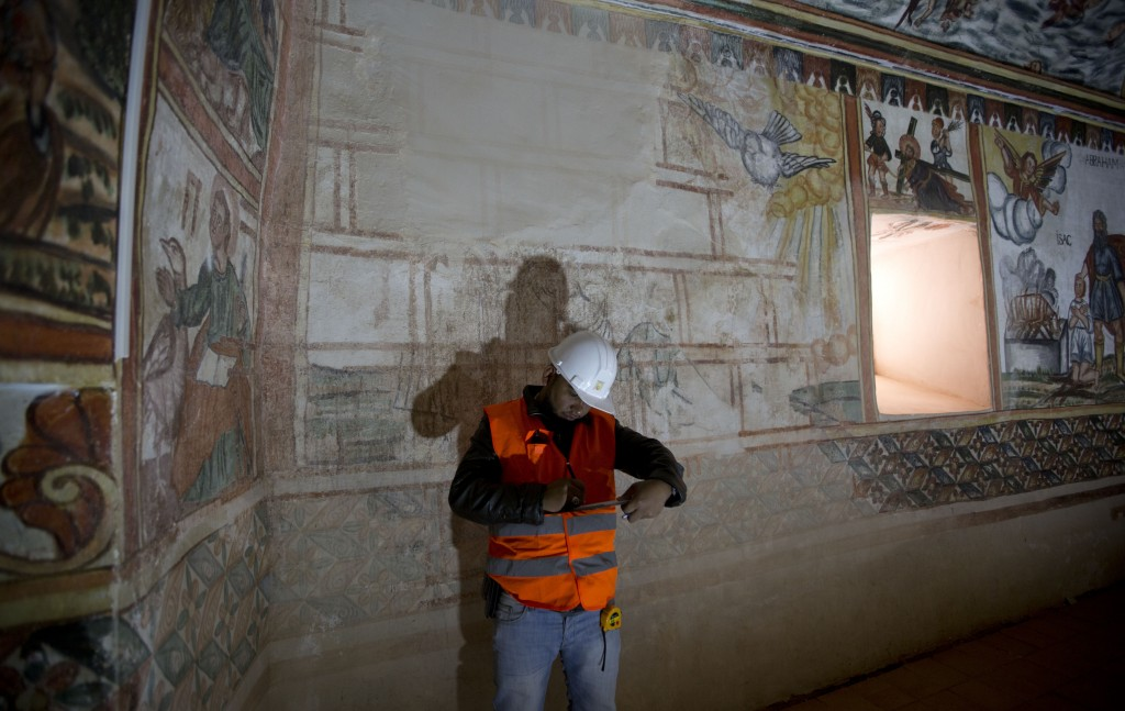 In this Feb. 9, 2019 photo, an architect, expert in restoration, writes in his notebook as he inspects damage done to the murals by humidity and time,
