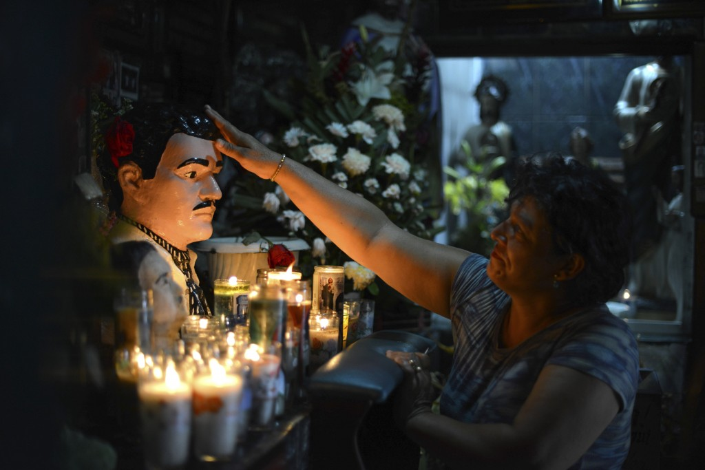 FILE - In this July 20, 2015 file photo, Guadalupe Tadeo de Valenzuela prays to folk-saint Jesus Malverde, to heal her sick daughter in the saint's ch