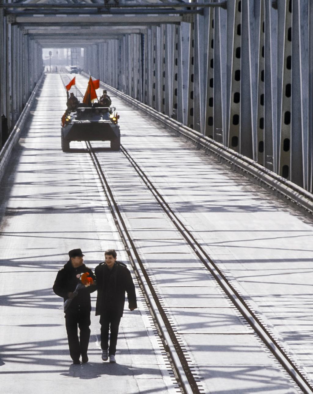 In this photo taken on Feb. 15, 1989, Lt. Gen. Boris Gromov, left, with his son Maxim, walk across a bridge over the Amy Darya River, at Termez, Uzbek...